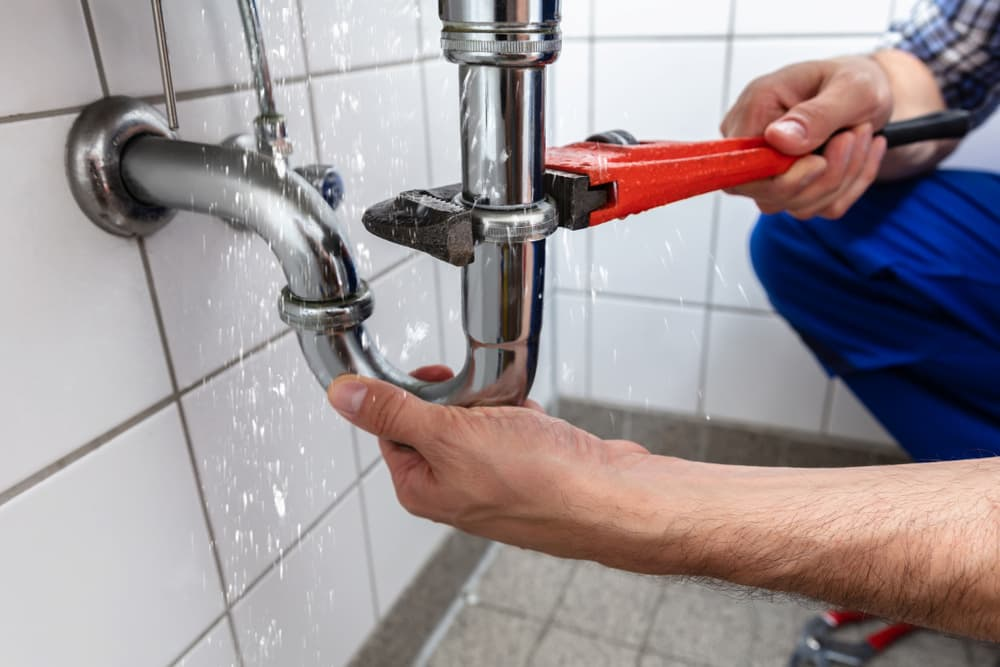 Rooter Man employee using a wrench to fix a leaky sink pipe